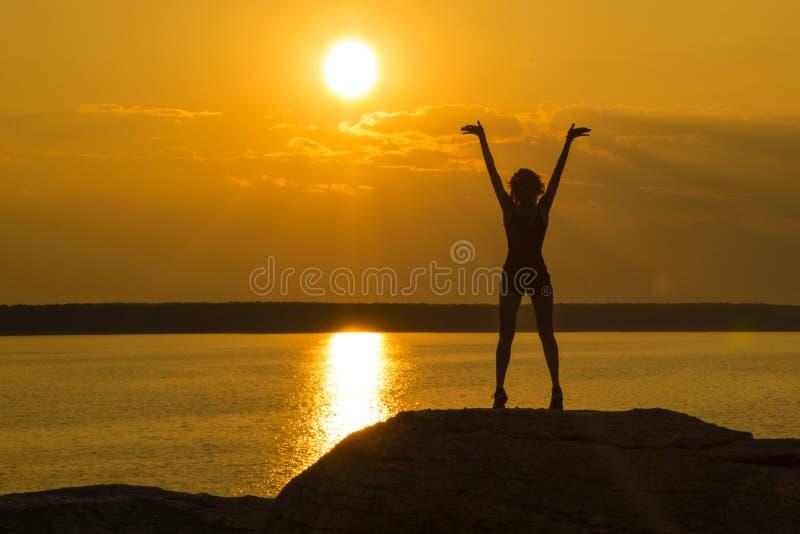En ung spenslig flicka står överst av ett berg som rymmer upp hennes händer in mot solen i solnedgången royaltyfria bilder