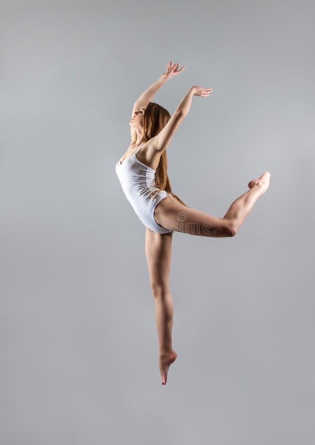 En ung spenslig flickagymnast hoppar högt i dansen royaltyfri bild