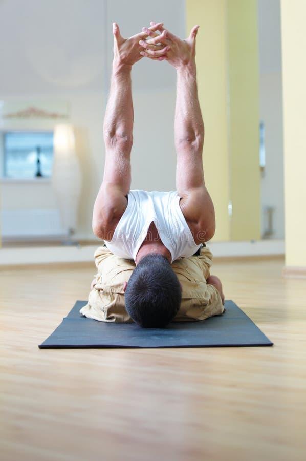 En ung stark man som gör sammanträdeyoga, övar - adhomukhavirasana i yogastudion arkivbild