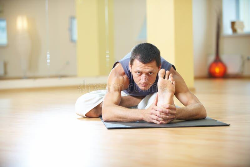 En ung stark man som gör yoga, övar - krökningen för lotusblomma Ardha den Padma Paschimottanasana placerade för den framåt halva arkivfoton