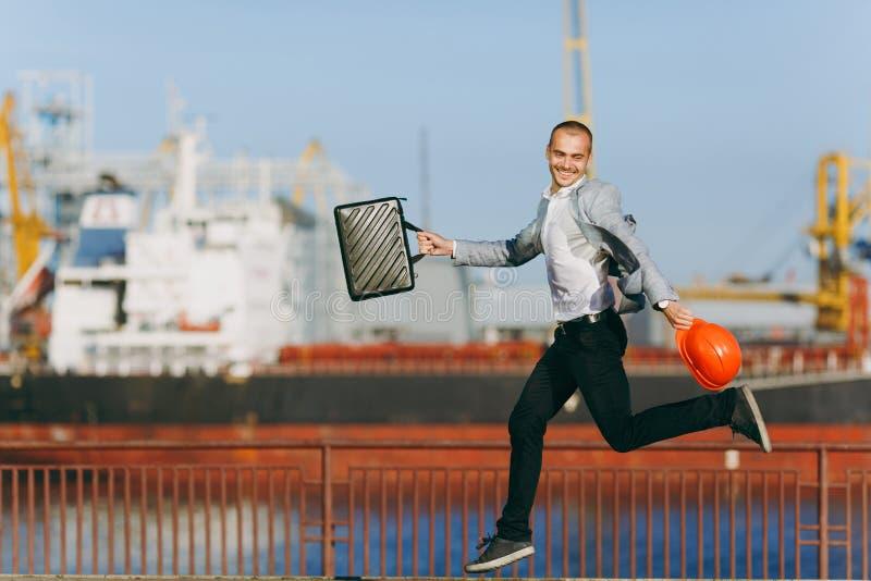 En ung stilfull man i en skyddande hjälm mot bakgrunden av en hamnstad arkivbild