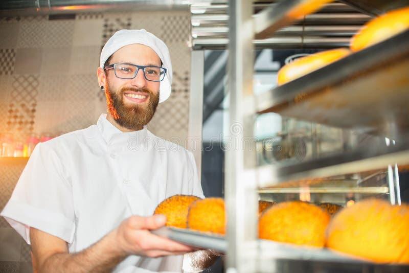 En ung stilig bagare tar ut varm ny bakning från ugnen i bagerit royaltyfri bild