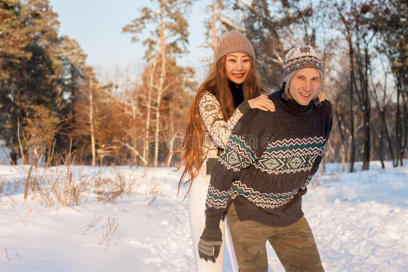 En ung stilig man av det europeiska utseendet och en ung asiatisk flicka i parkerar på naturen i vinter A royaltyfria bilder