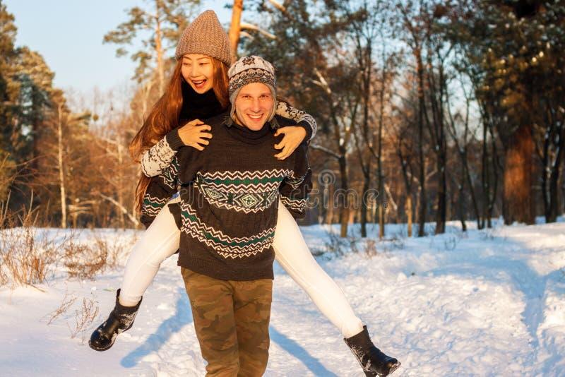 En ung stilig man av det europeiska utseendet och en ung asiatisk flicka i parkerar på naturen i vinter A arkivbild