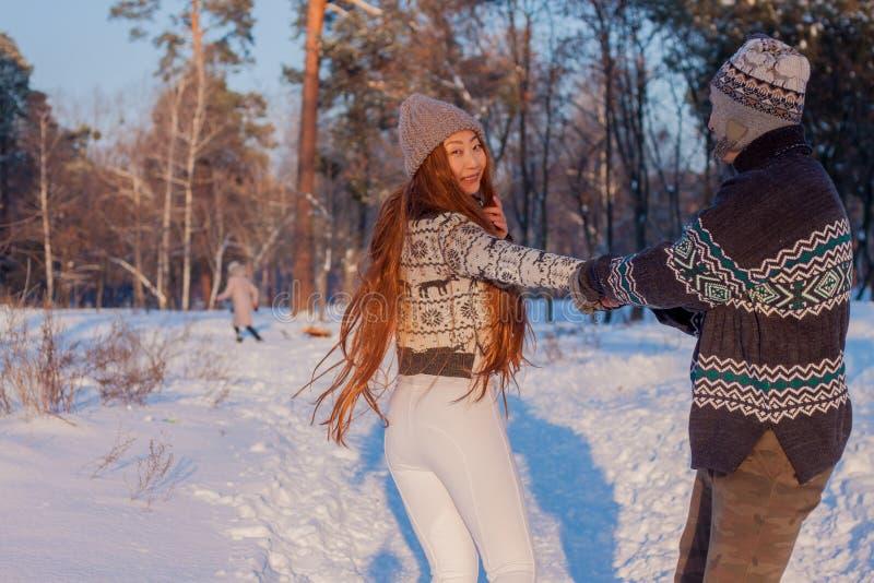 En ung stilig man av det europeiska utseendet och en ung asiatisk flicka i parkerar på naturen i vinter royaltyfri fotografi