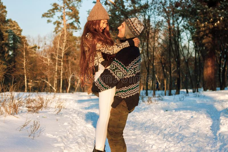 En ung stilig man av det europeiska utseendet och en ung asiatisk flicka i parkerar på naturen i vinter royaltyfri foto