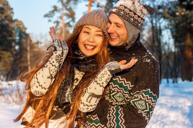 En ung stilig man av det europeiska utseendet och en ung asiatisk flicka i parkerar på naturen i vinter royaltyfria bilder
