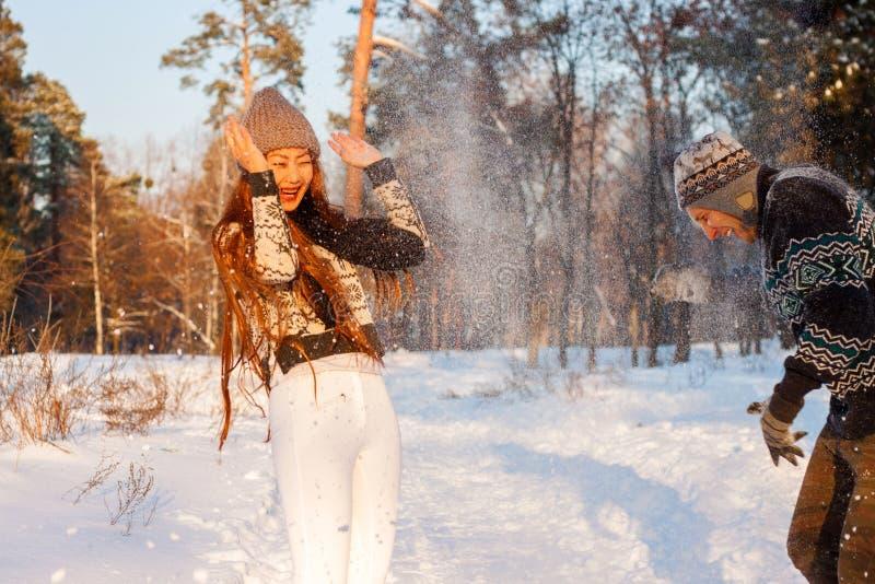 En ung stilig man av det europeiska utseendet och en ung asiatisk flicka i parkerar på naturen i vinter royaltyfria foton