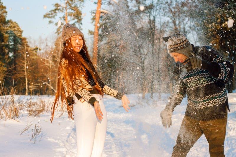 En ung stilig man av det europeiska utseendet och en ung asiatisk flicka i parkerar på naturen i vinter fotografering för bildbyråer