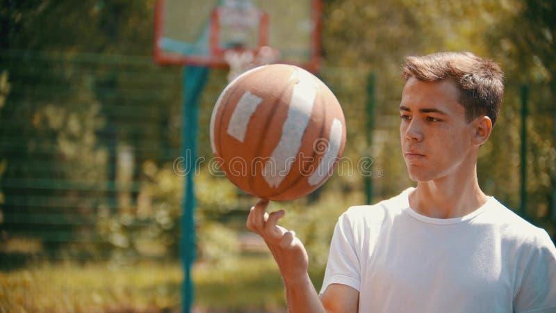 En ung stilig man, i det vita skjortaanseendet på en sportjordning och rotering av basketbollen på hans finger royaltyfri bild