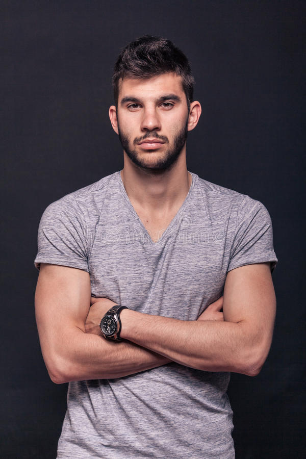 En ung stilig man, korsade armar, royaltyfri foto