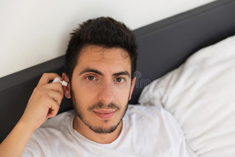 En ung stilig man sitter i hans säng arkivfoton