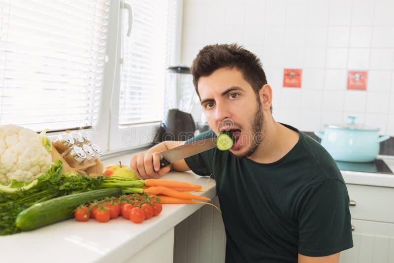 En ung stilig man sitter i köket och äter motvilligt grönsaker royaltyfria foton