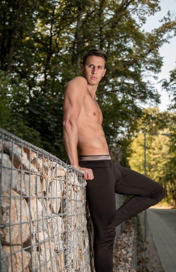 En ung stilig man som poserar, shirtless mus för skogkonditionkropp royaltyfria bilder