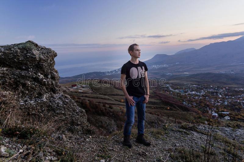En ung stilig man står hög i bergen och blickarna på solnedgången arkivfoton