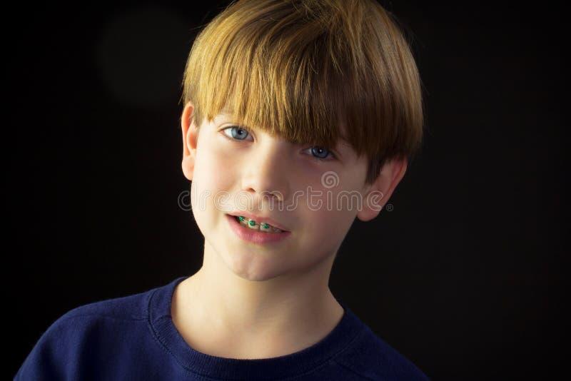 En ung stilig pojke och hans gröna hänglsen fotografering för bildbyråer