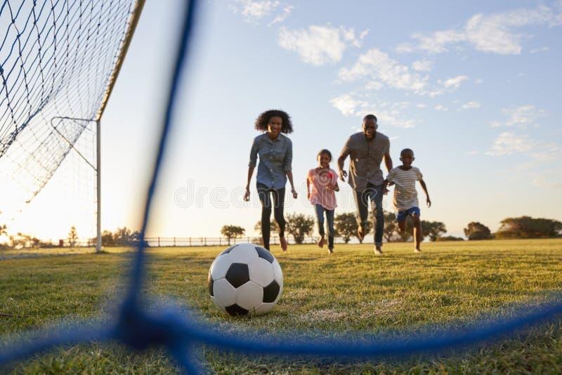En ung svart familj som jagar en fotboll under en lek arkivbilder