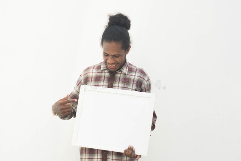 En ung svart man som rymmer det vita brädet med isolerad bakgrund i det vita tomma vita brädet för din design arkivbild