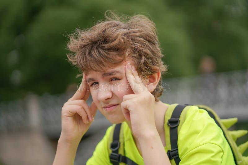 En ung tonåringgrabb lider från en huvudvärk han håller hans händer till hans huvud och ryckningar av obehag som sitter på nature royaltyfria foton