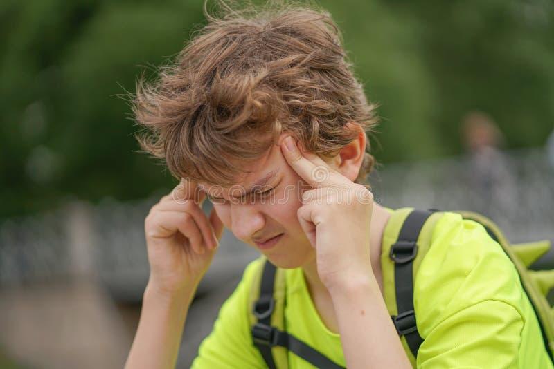 En ung tonåringgrabb lider från en huvudvärk han håller hans händer till hans huvud och ryckningar av obehag som sitter på nature royaltyfri foto
