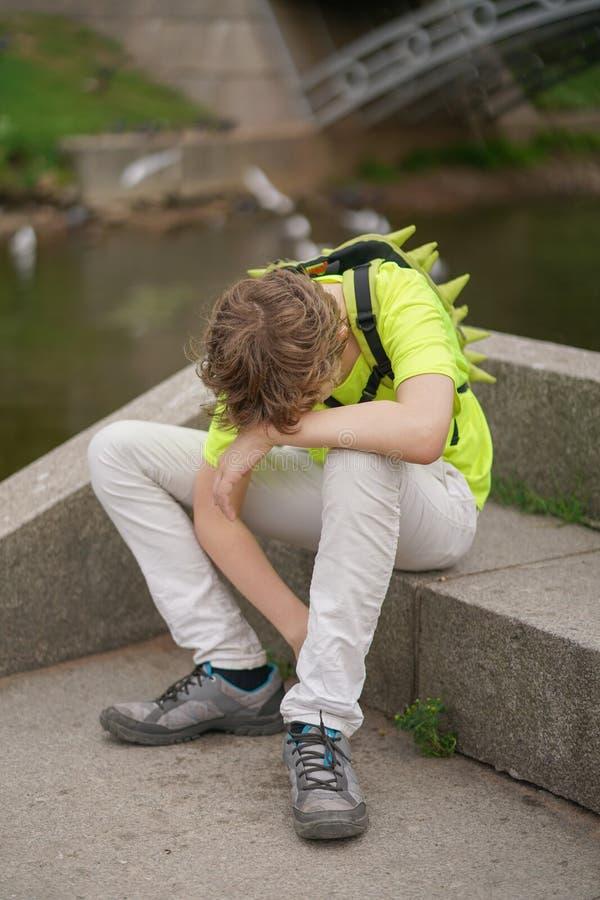 En ung tonåringgrabb lider från en huvudvärk han håller hans händer till hans huvud och ryckningar av obehag som sitter på nature royaltyfri bild