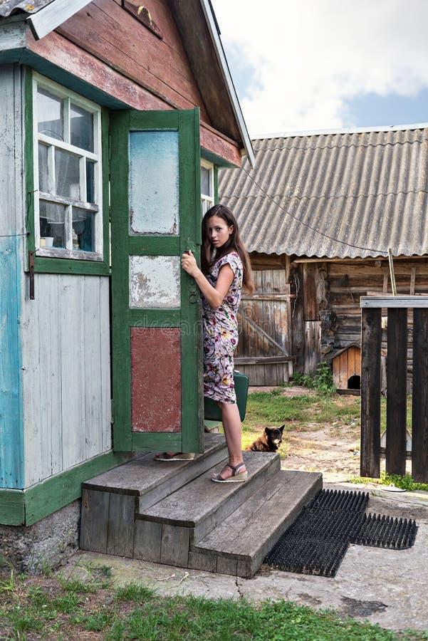 En ung trendig kvinna i en retro klänning för tappning stiger momenten av ett sjaskigt hus för by med skjul arkivbilder