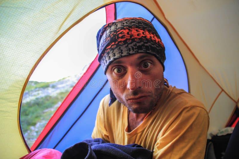 En ung turist- grabb sitter inom ett gult tält på campingplatsen royaltyfri fotografi