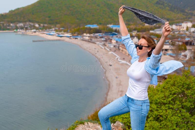 En ung turist- kvinna kl?ttrade till ?verkanten av berget Sinnesr?relser av gl?dje och lycka Berg och hav i bakgrunden close arkivfoton