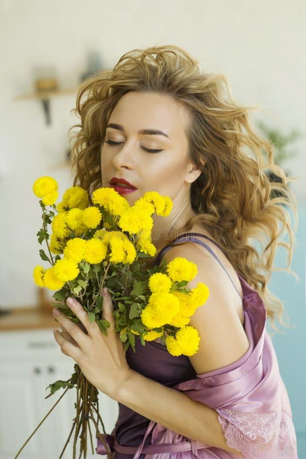 En ung, vacker blond kvinna i rosa morgongäss med gula blommor i hennes kök arkivfoton