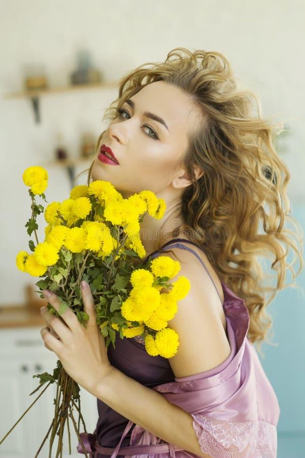 En ung, vacker blond kvinna i rosa morgongäss med gula blommor i hennes kök royaltyfria bilder