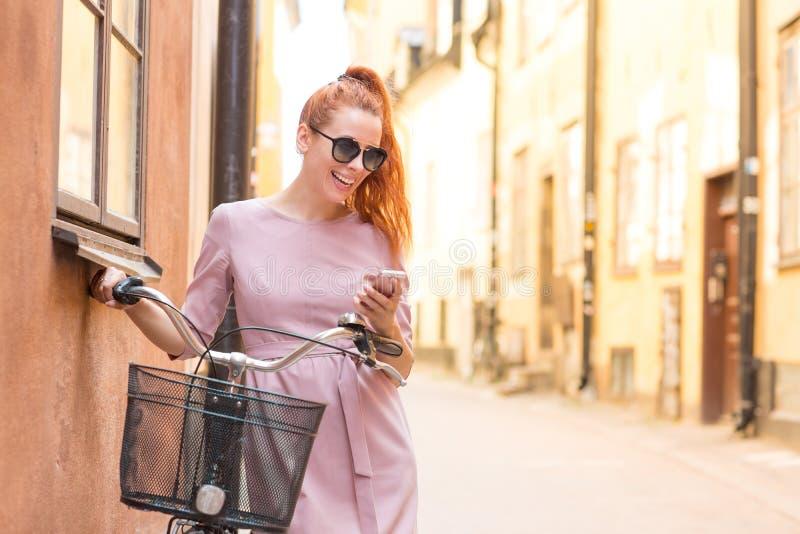 En ung vacker kvinna med cykel på en gata med smartphone royaltyfria bilder
