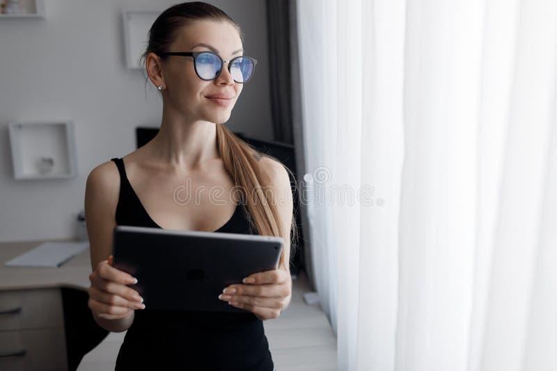 En ung vacker kvinna tillbringar tid med att arbeta på en dator som uppfyller kraven på självisoleringsläge under en epidemi arkivfoton