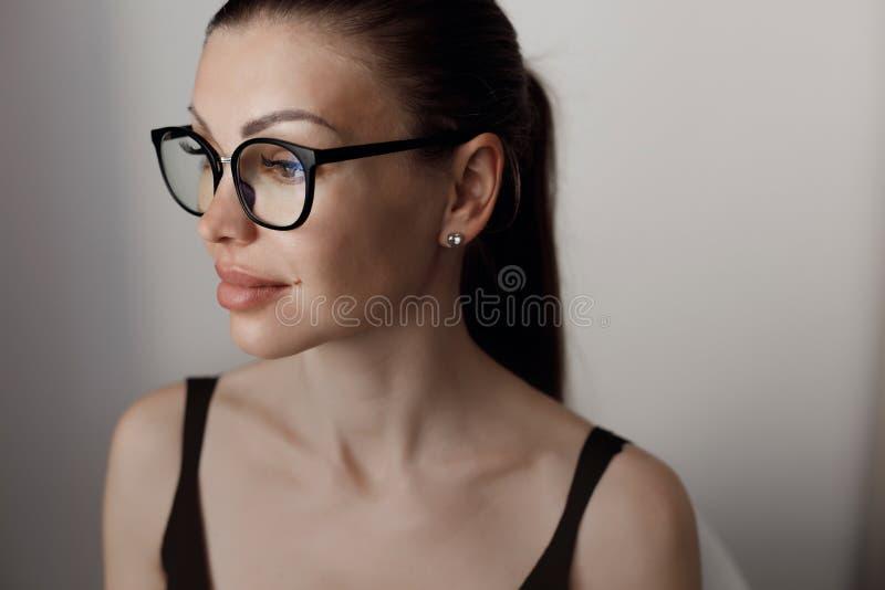 En ung vacker kvinna tillbringar tid med att arbeta på en dator som uppfyller kraven på självisoleringsläge under en epidemi arkivfoto
