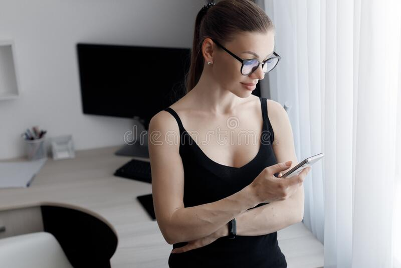 En ung vacker kvinna tillbringar tid med att arbeta på en dator som uppfyller kraven på självisoleringsläge under en epidemi royaltyfri fotografi