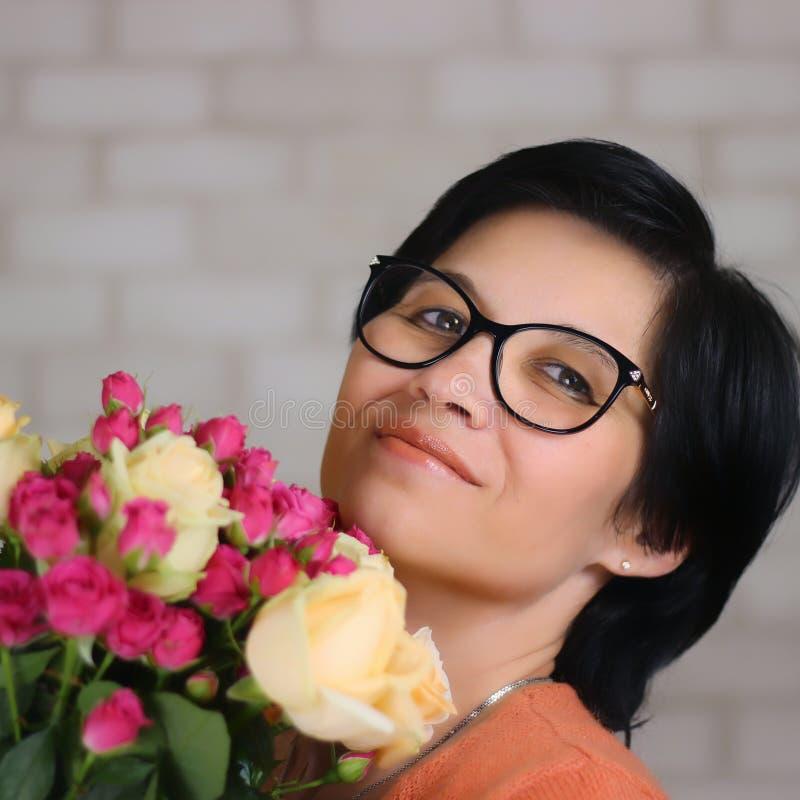 En ung, vacker, lycklig brunettkvinna i glasögon med en blombukett ser ut med ett lyckligt utseende Övertonad Kopiera utrymme arkivbild
