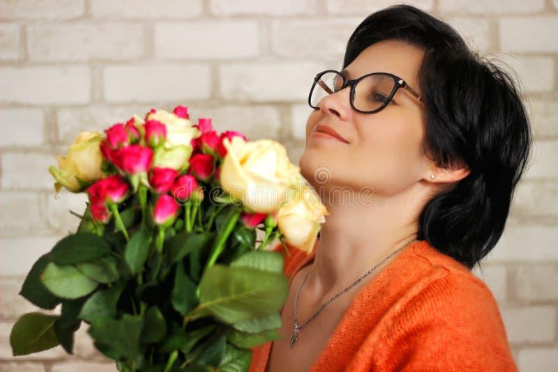 En ung, vacker, lycklig brunettkvinna i glasögon med blommor ser blommorna med ett lyckligt utseende royaltyfria bilder