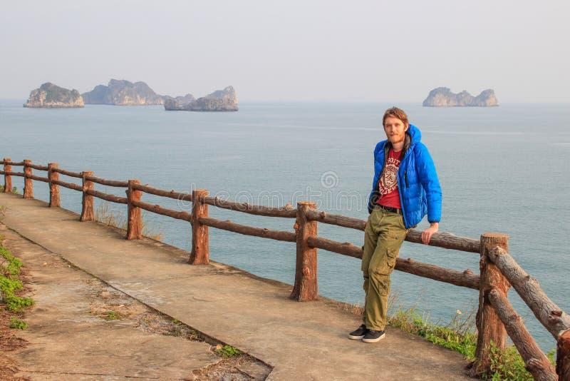 En ung vit attraktiv man som är blond med ett skägg i en blått ner omslagsställningar mot bakgrunden av en klippa och havet i mum fotografering för bildbyråer