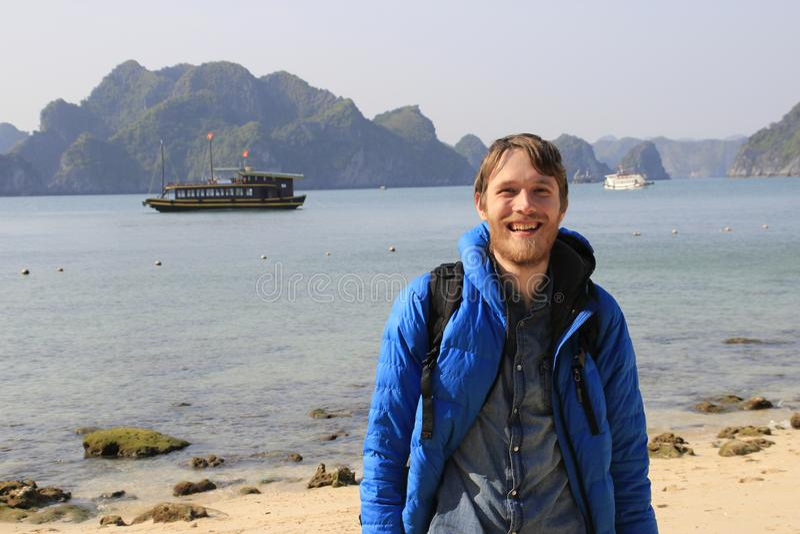 En ung vit attraktiv man som är blond med ett skägg i en blått ner omslagsställningar mot bakgrunden av en klippa och havet i mum royaltyfri foto