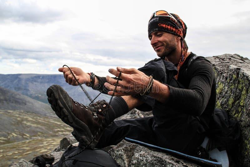 En ung vit Caucasian man med en obetydlig unshavenness förbereder sig för en ny dag av att fotvandra i bergen och band av skosnör arkivfoto