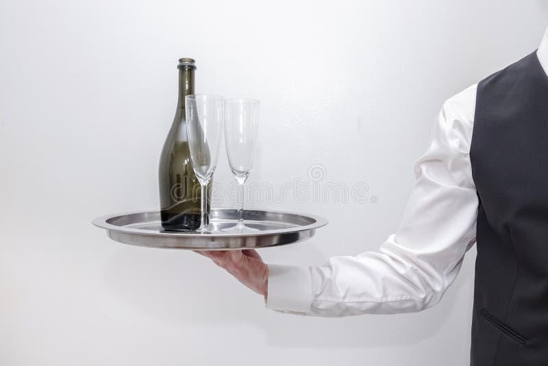 En uppassare/en betjänt som bär ett silvermagasin med en flaska av champagne och två exponeringsglas royaltyfria foton