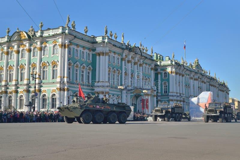 En uppdelning av infanteri på APCEN med en röd flagga och lastbilar på arkivfoton