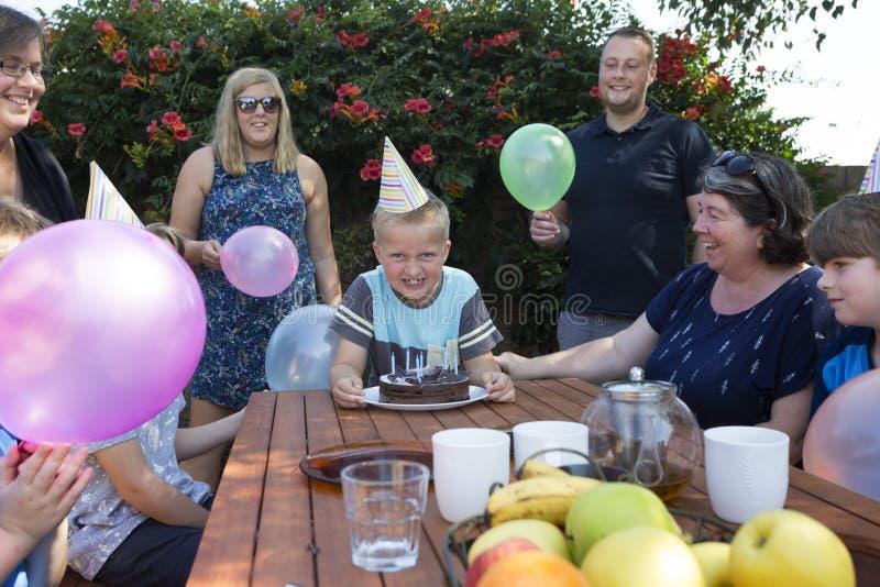 En upphetsad pojke med familjen runt om honom som firar en födelsedag arkivbild