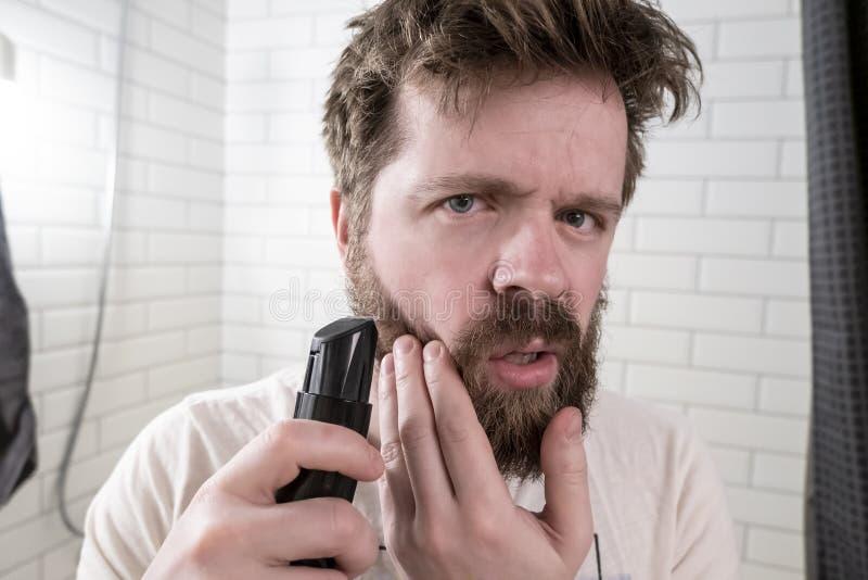 En uppriven ung man ser i spegeln på hans lurviga frisyr och tjocka skägg och ska göra sig en frisyr med arkivfoto