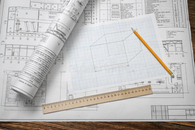 En uppsättning av öppna och hoprullade ritningar på trätabellbakgrund med en blyertspenna och en linjal som beside ligger fotografering för bildbyråer