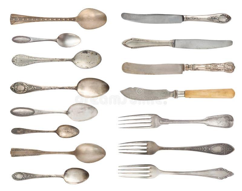 En uppsättning av antikt fint bestick Tappningskedar, gafflar och knivar som isoleras på en vit bakgrund arkivbilder
