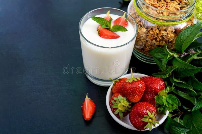 En uppsättning av en produkt för en läcker sund frukost: granola yoghurt, nya jordgubbar arkivfoto