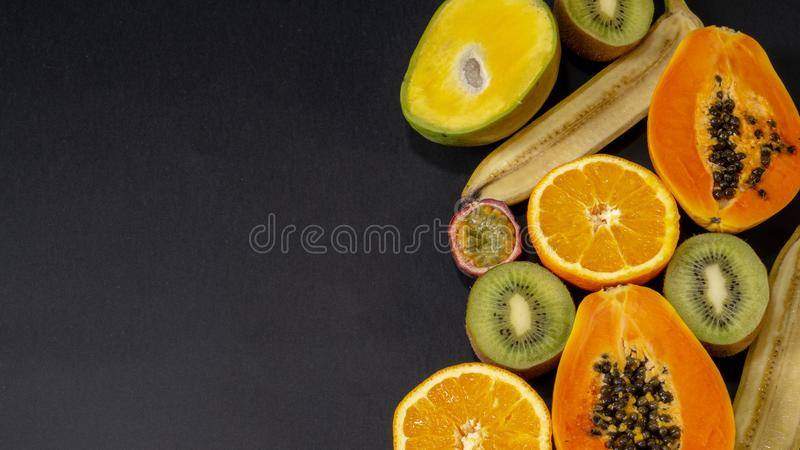En uppsättning av frukter, frukt är på det lämnade högra och fria utrymmet, svart bakgrund, fotografering för bildbyråer