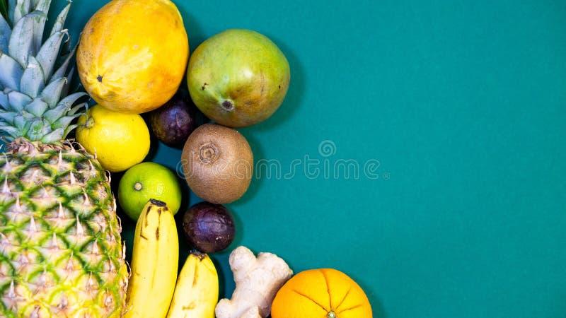 En uppsättning av frukter, frukt är på vänstersidan och ett fritt utrymme på rätten, grön bakgrund royaltyfri foto
