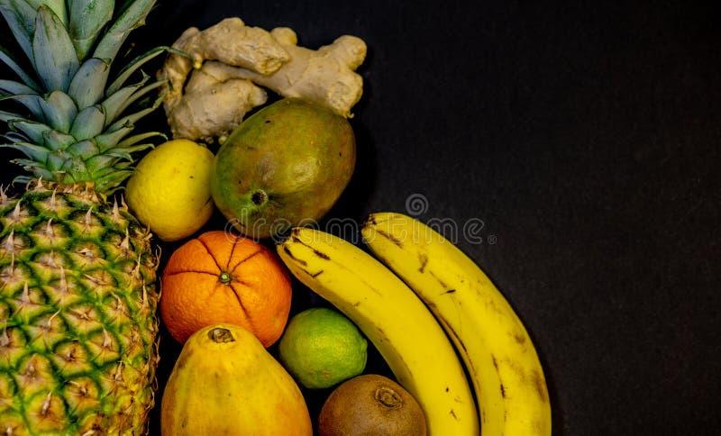En uppsättning av frukter, frukt är på vänstersidan och ett fritt utrymme på rätten, svart bakgrund, ananasapelsin arkivbild