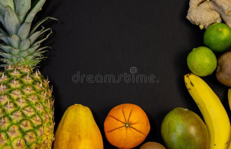 En uppsättning av frukter, fruktzarbrosani runt om fotoet, i mitt av fritt utrymme, svart bakgrund arkivbild